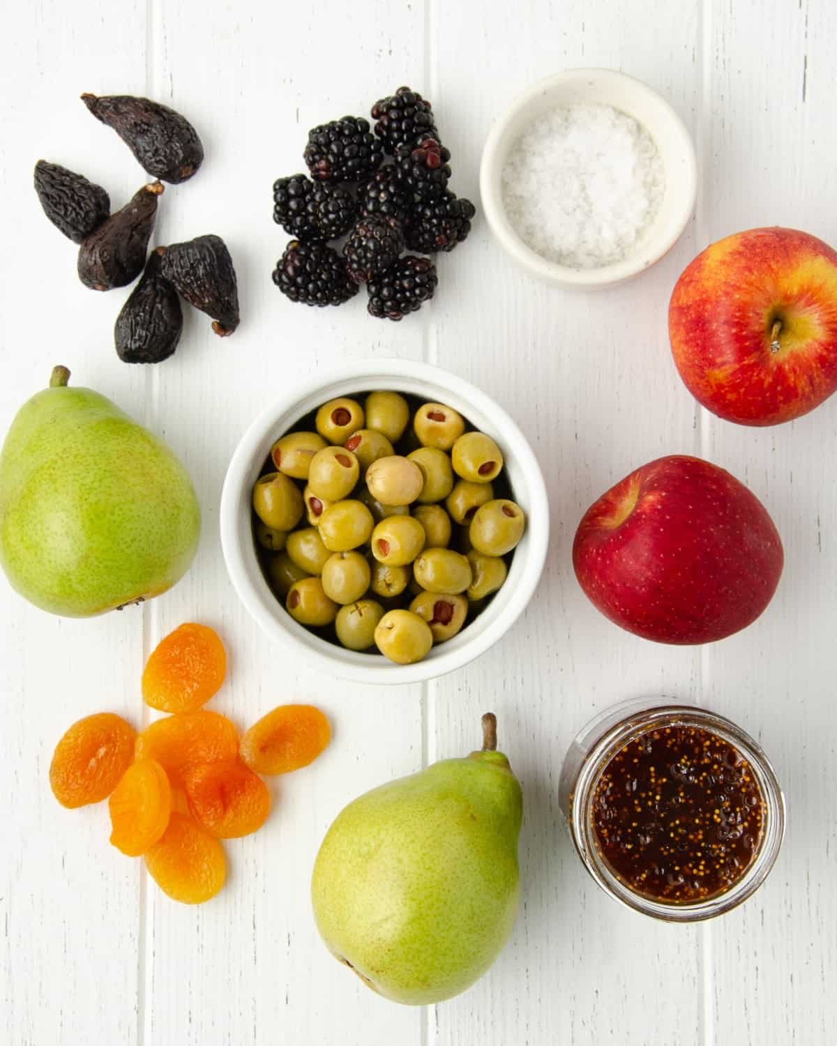 ideas for add ons for a charcuterie board: dried figs, fresh blackberries, a bowl of flakey salt, two apples, a bowl of fig spread, a large bowl of olives, two pears, and a handful of dried apricots