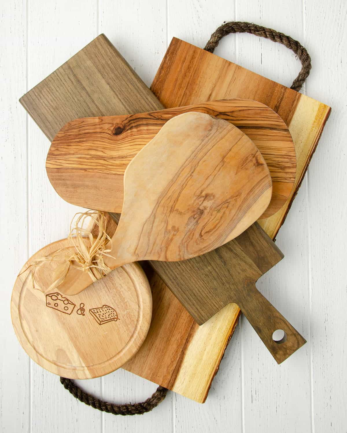 a group of five different wooden cheese boards on top of a white table