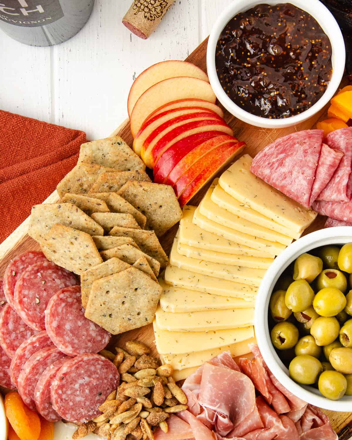 a close up of sliced apples, sliced dill havarti, gluten free crackers, salami, and a bowl of fig spread on a charcuterie board