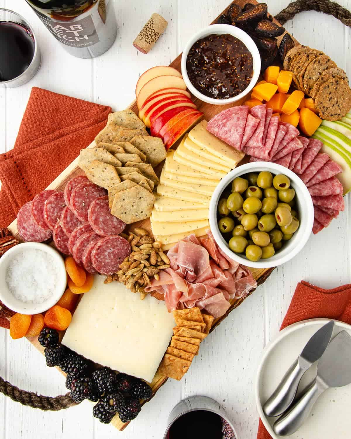 a gluten free charcuterie board sit-in on a white wooden table with orange linens and a plate with cheese knives sitting to the bottom with a bottle of red wine and two glasses filled with wine to the top and bottom of the image