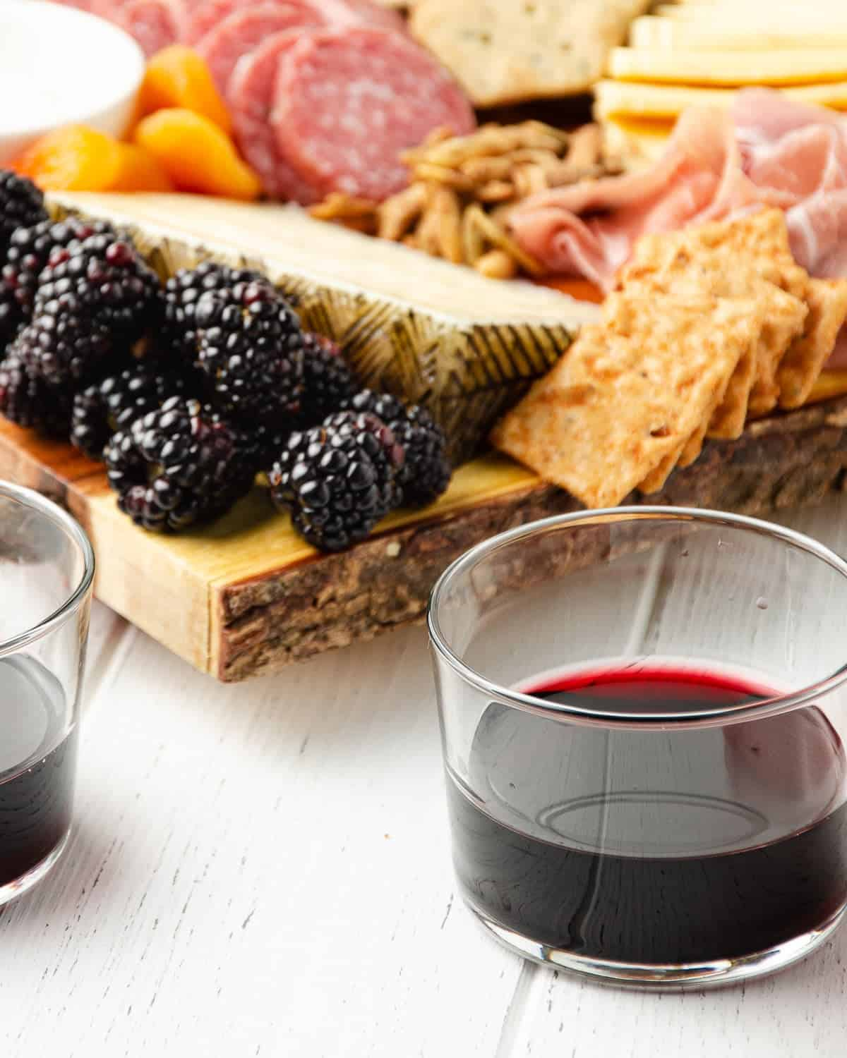 a close up image of two red wine glasses in front of a cheese board featuring manchego, blackberries, crackers and cured meats behind
