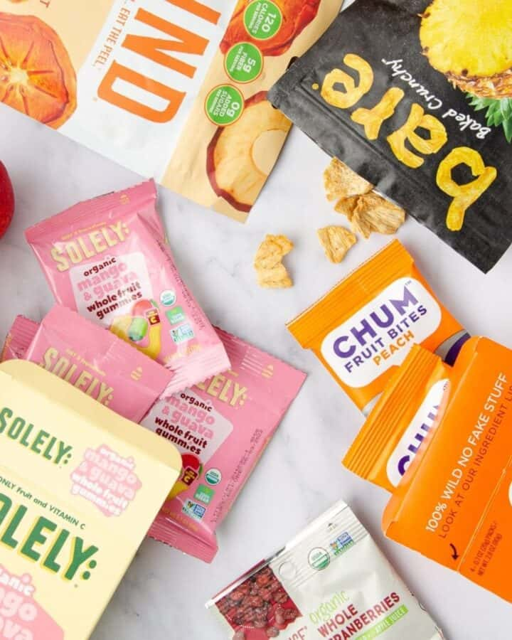 a featured image of dairy free gluten free snacks featuring apples, oranges, a bag of pineapple chips, a bag of dehydrated fruits, two boxes of fruit gumies, and a bag of dried cranberries