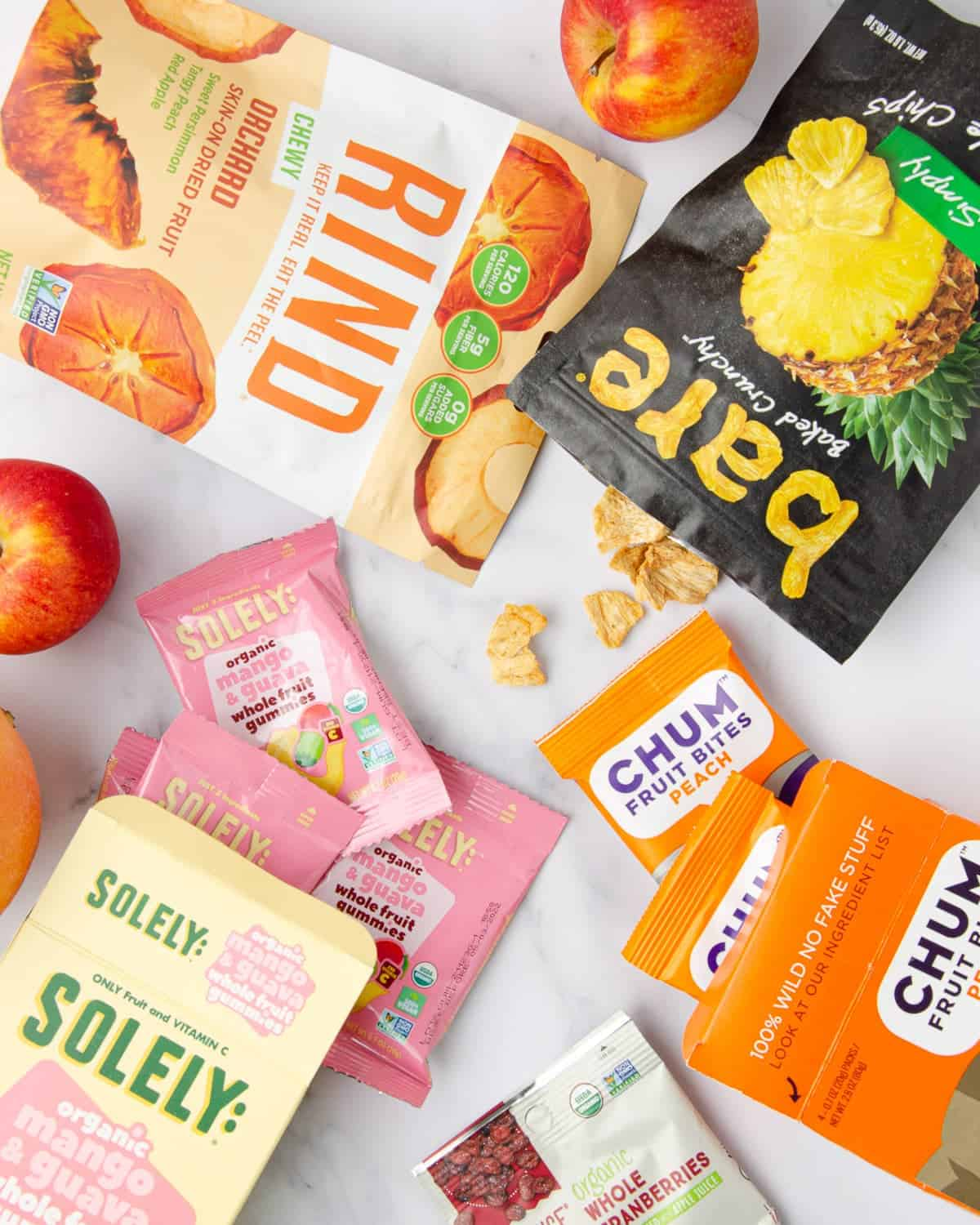 dairy free gluten free snacks featuring apples, oranges, a bag of pineapple chips, a bag of dehydrated fruits, two boxes of fruit gumies, and a bag of dried cranberries