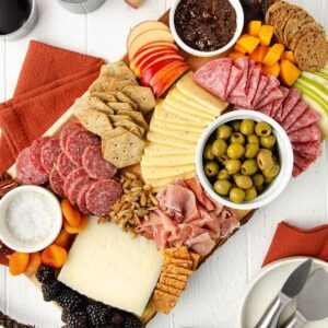 featured image of a gluten free charcuterie board sit-in on a white wooden table with orange linens and a plate with cheese knives sitting to the bottom