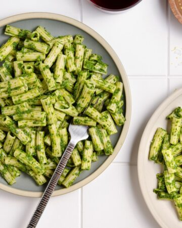 Two plates of pasta with green pasta sauce with a fork.