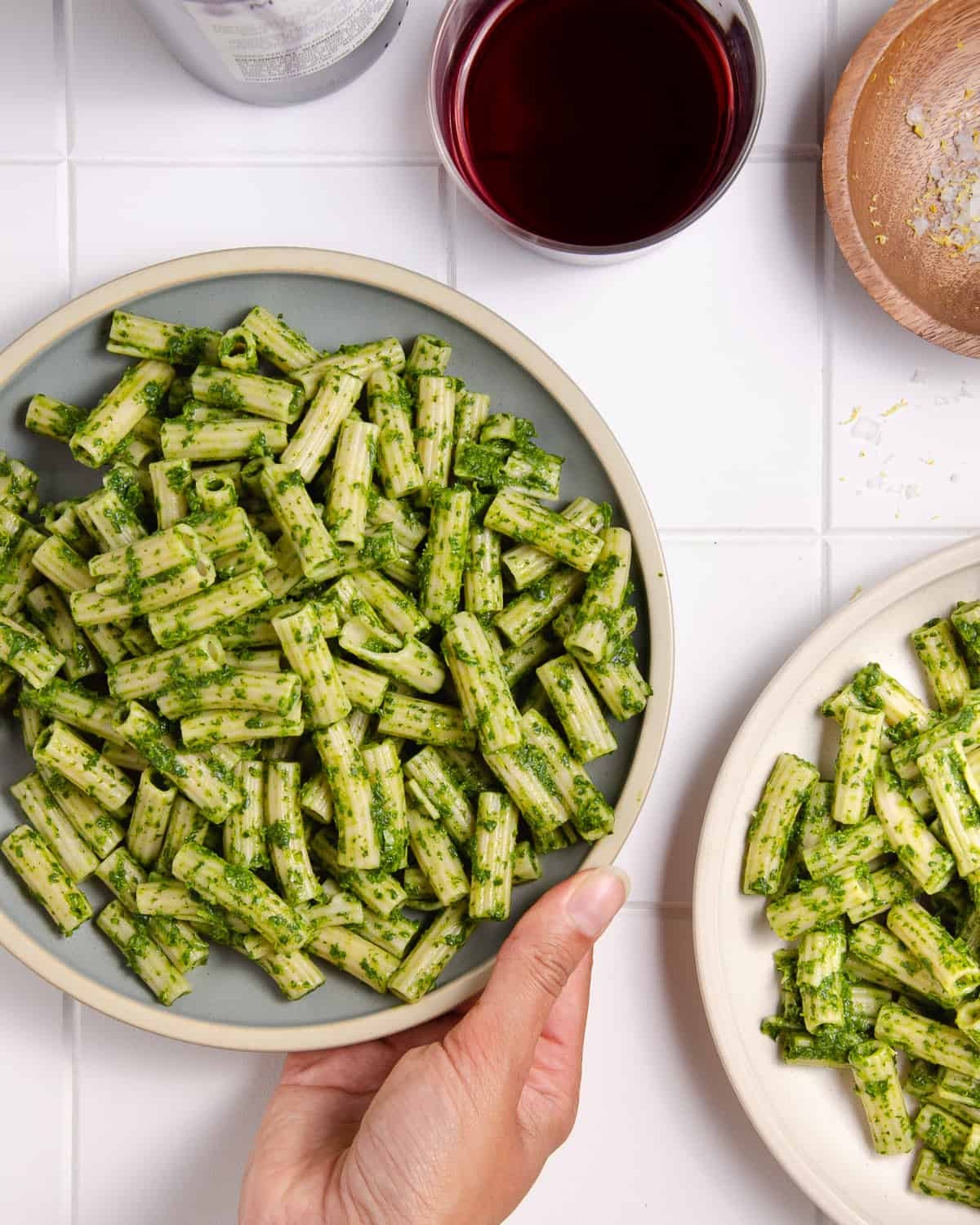 A hand picking up a plate of pasta with green sauce.