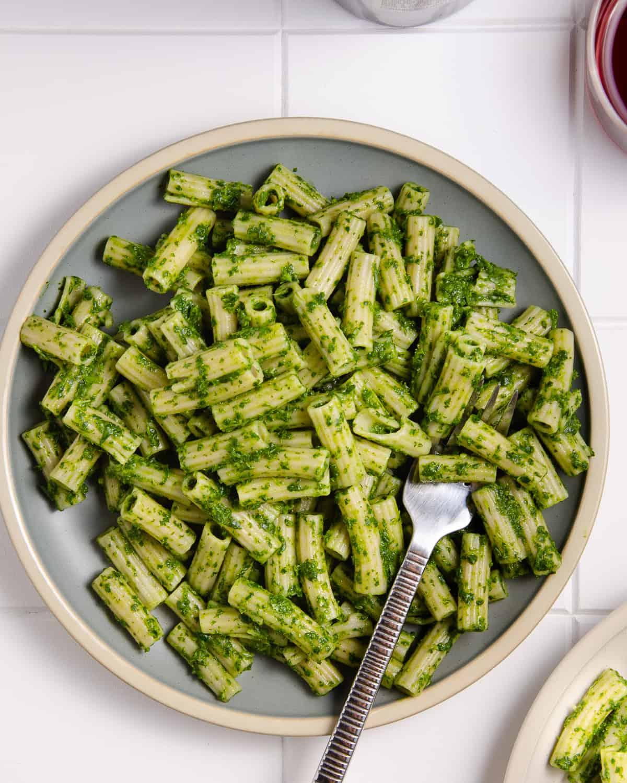 Green pasta sauce on gluten free pasta on a blue plate.
