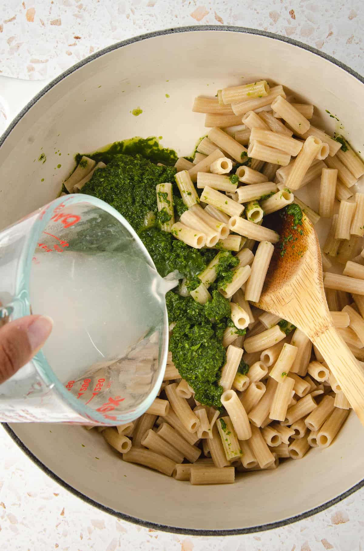 Pouring reserved pasta water onto cooked pasta in a pot.