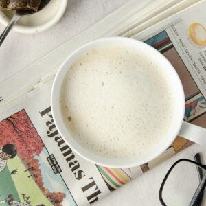 A close up of a London Fog Tea Latte on top of a newspaper.