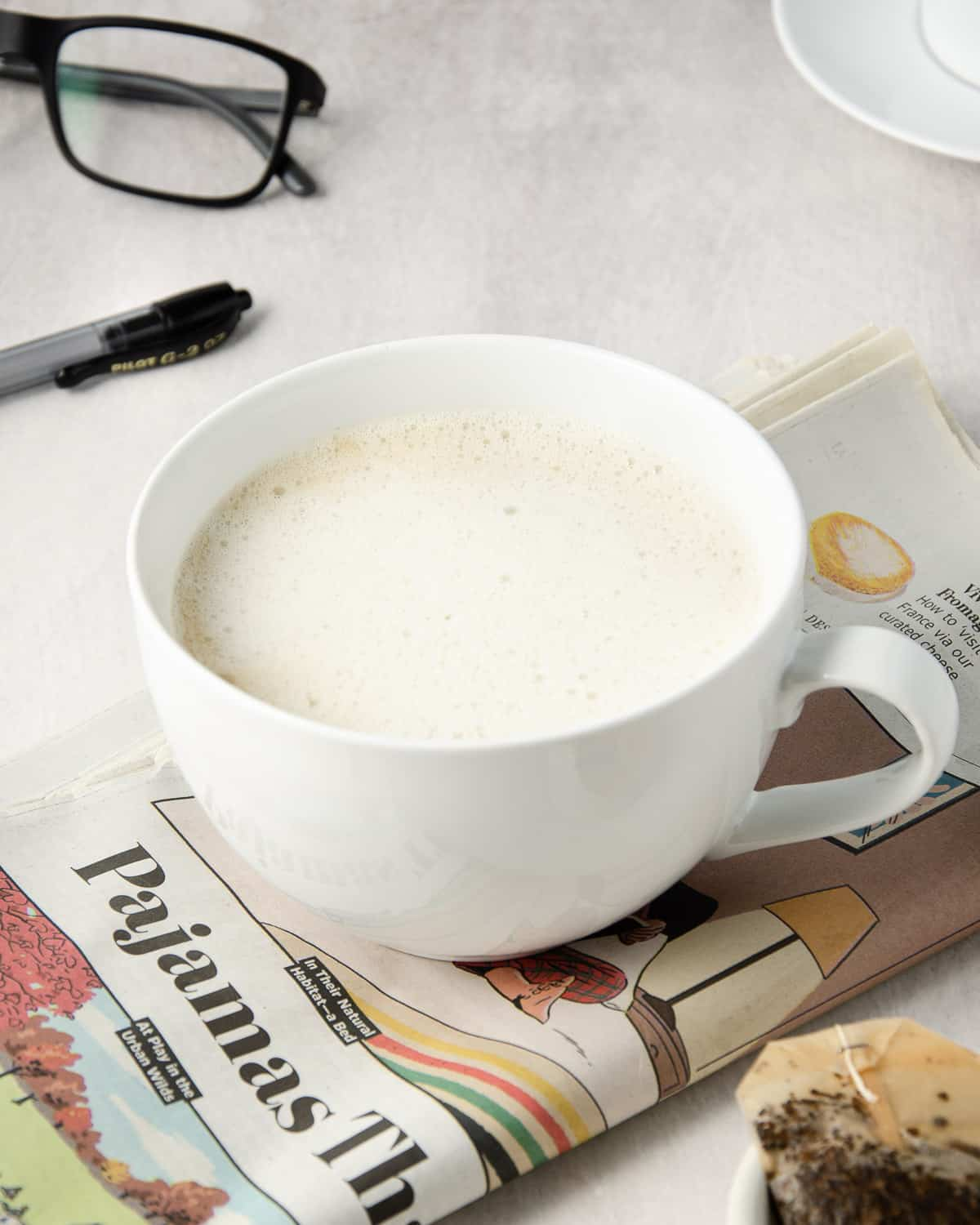 An angled view of earl grey latte in a mug on top of a newspaper.