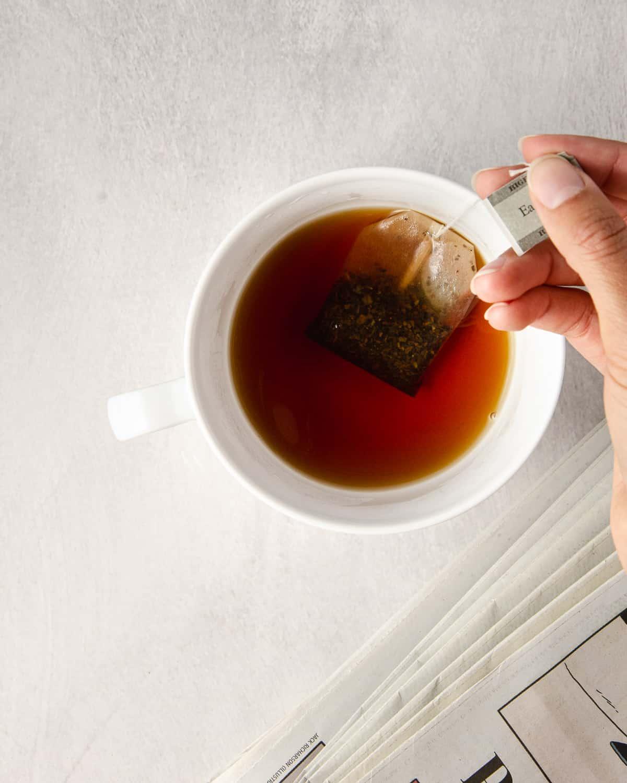 Letting an earl grey tea bag seep in boiling water in a mug.