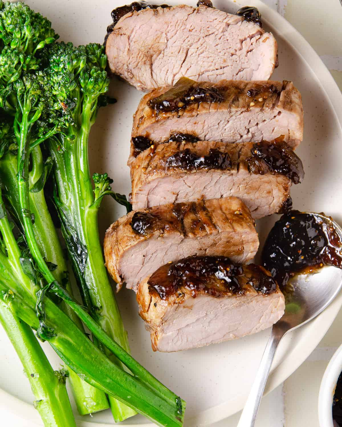 Close up of pork tenderloin slices with a spoon of balsamic fig glaze to the side.