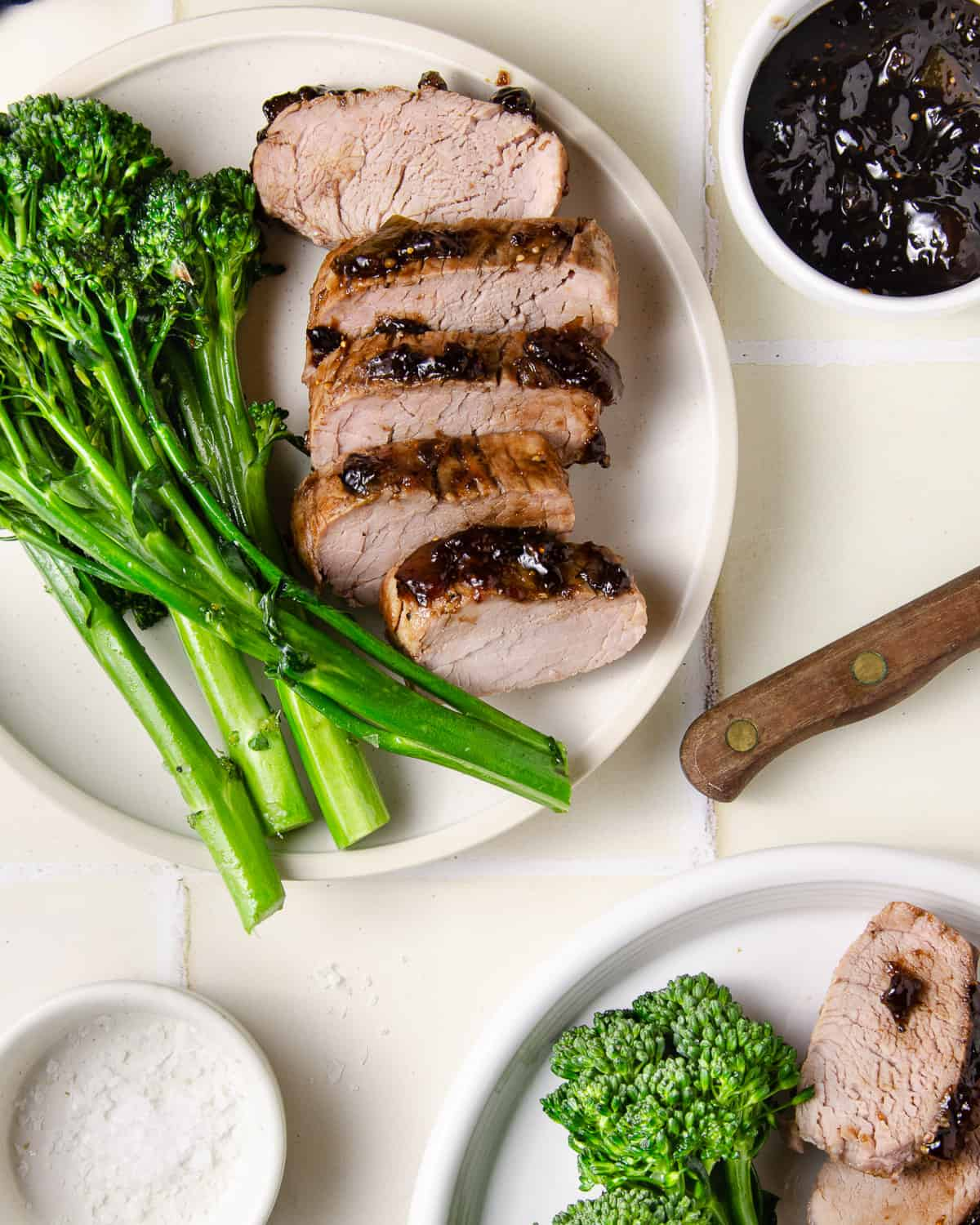 Two plates of pork tenderloin with broccolini and fig balsamic glaze.