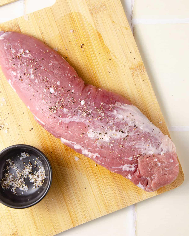 Seasoning a pork tenderloin with salt and pepper.