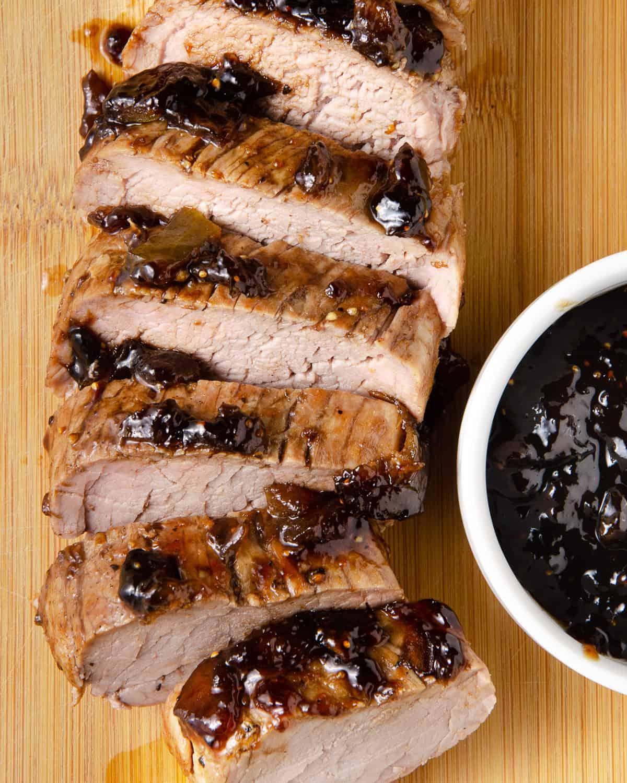 Close up of sliced pork tenderloin on a cutting board.