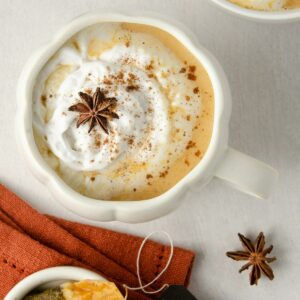 featured image of an overhead look of two latte mugs with pumpkin chai latte topped with coconut whipped cream and sprinkled with pumpkin pie spice and a star anise. to the below sits two chai tea bags.