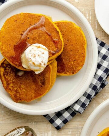 Featured image of three pumpkin pancakes on a plate.