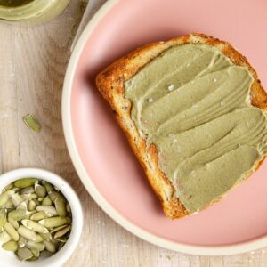 Pumpkin seed butter spread on a piece of toast on a pink plate.