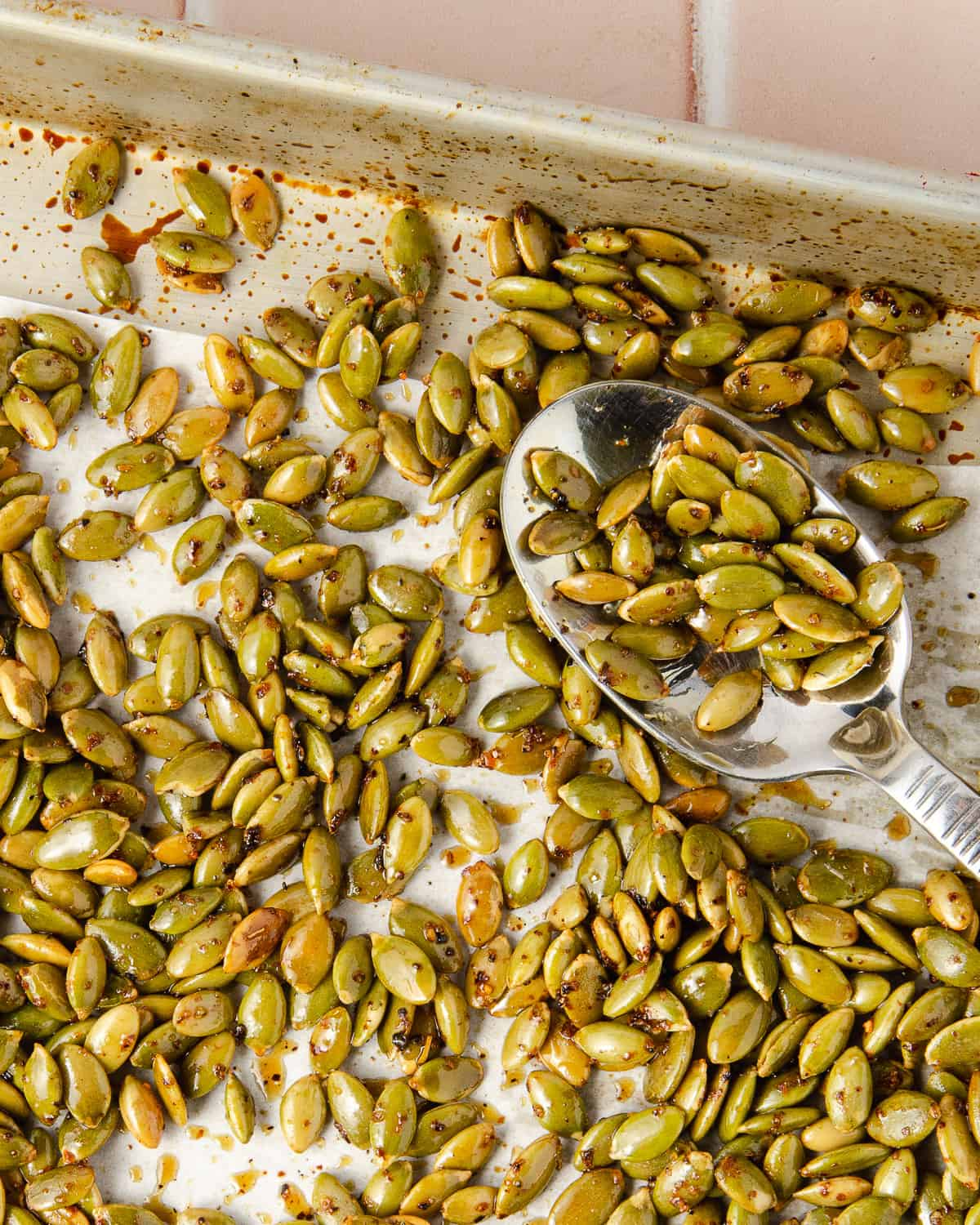 Close up of roasted pepitas on a baking tray with a spoon scooped out.