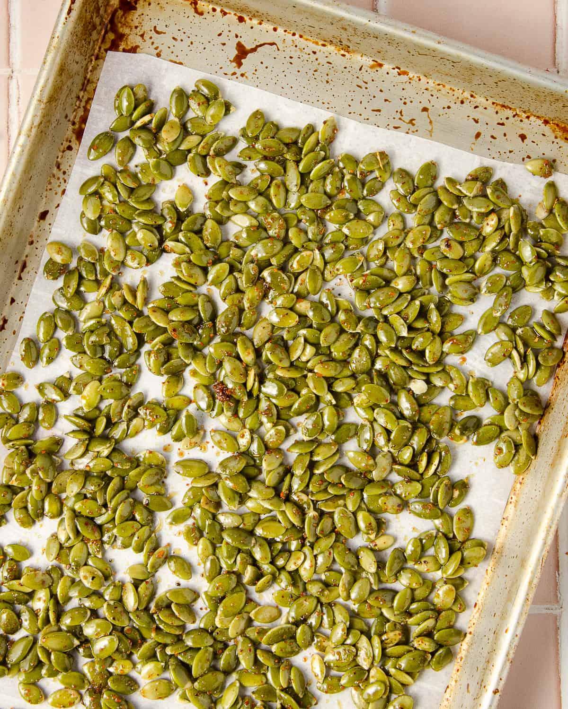 Raw pepitas with seasoning on a baking tray.