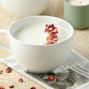 A featured image of a rose tea latte topped with rose petals.