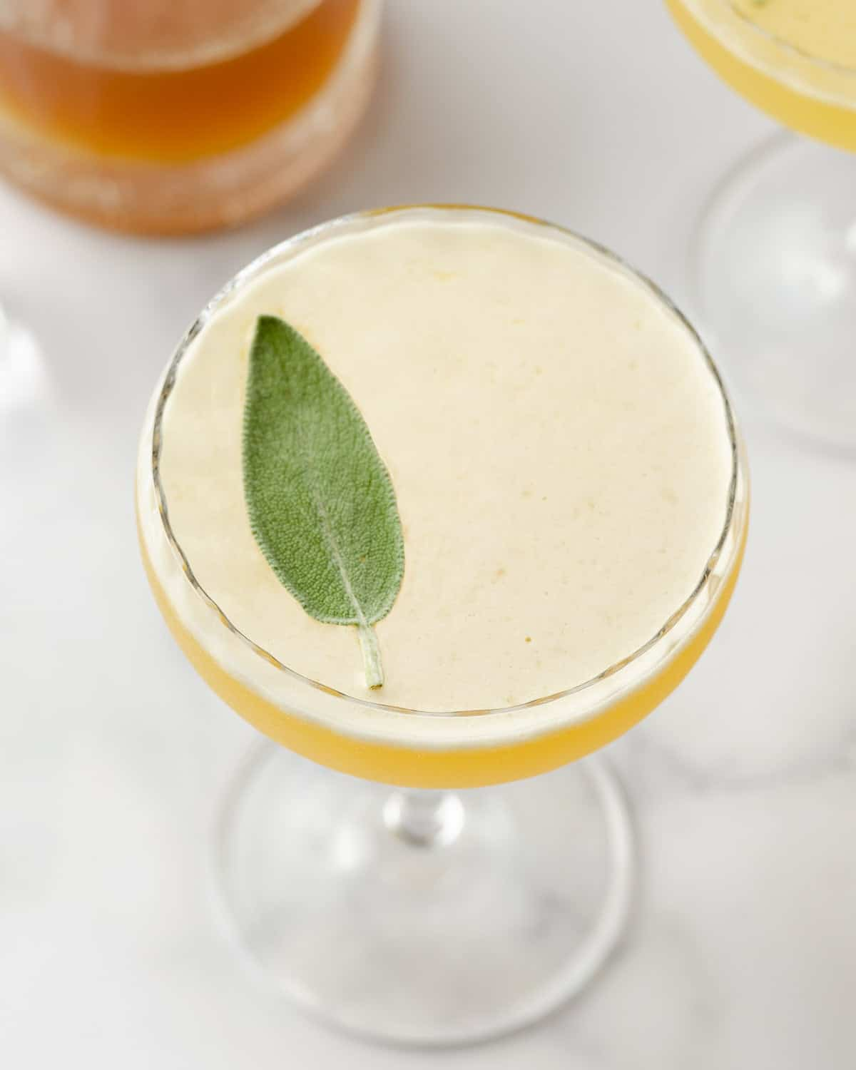 An angled view of a sage bee's knees cocktail garnished with a sage leaf.