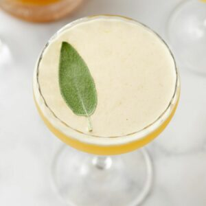 Featured image of close up of a sage leaf atop a bee's knees cocktail.