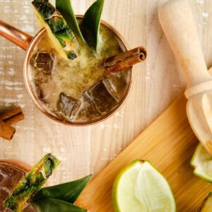 Featured Image of a pineapple spiced rum moscow mule: a copper mug garnished with a pineapple wedge, two pineapple leaves and a cinnamon stick. to the side is a lime wedge and a lime squeezer on top of a cutting board.