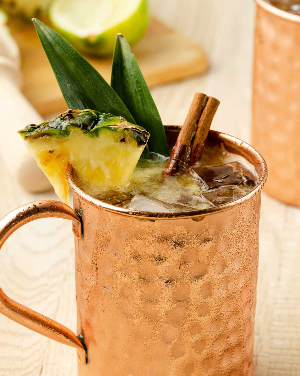 close up of the garnish on a rum moscow mule: a fresh pineapple wedge, pineapple leaves and a cinnamon stick.