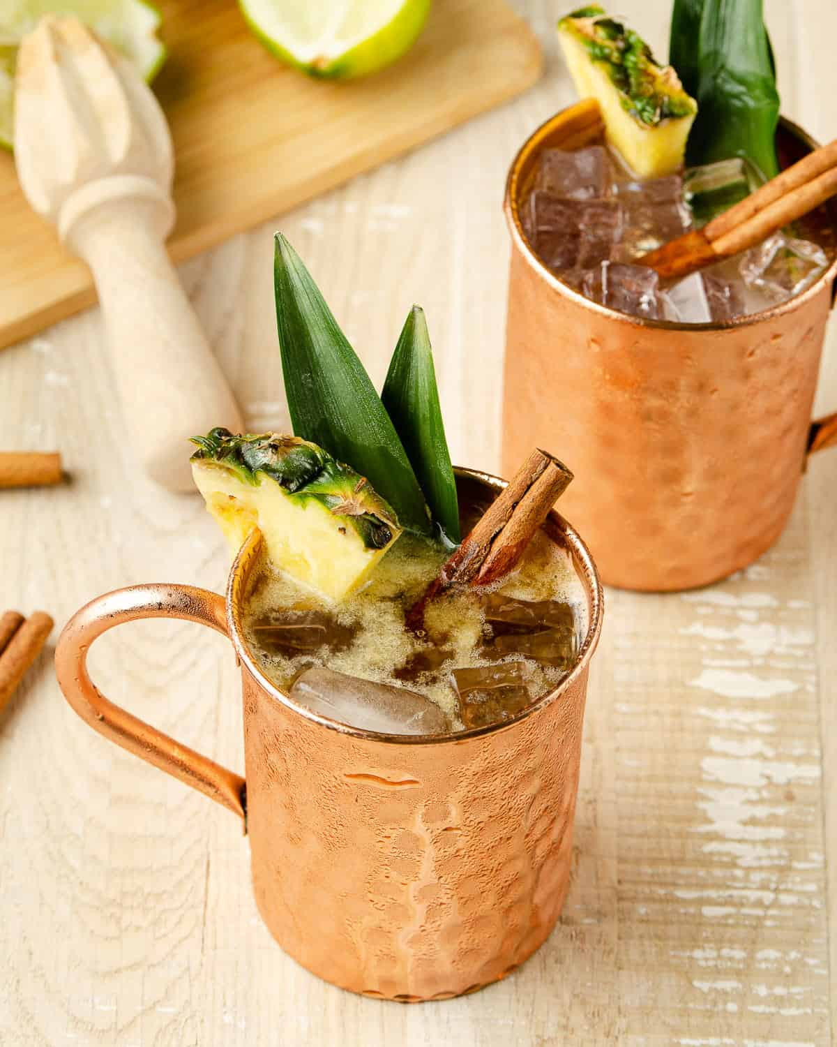 45 degree view of two tall moscow mule copper mugs garnished with pineapple pieces with a cutting board of two lime wedges squeezed to the back.