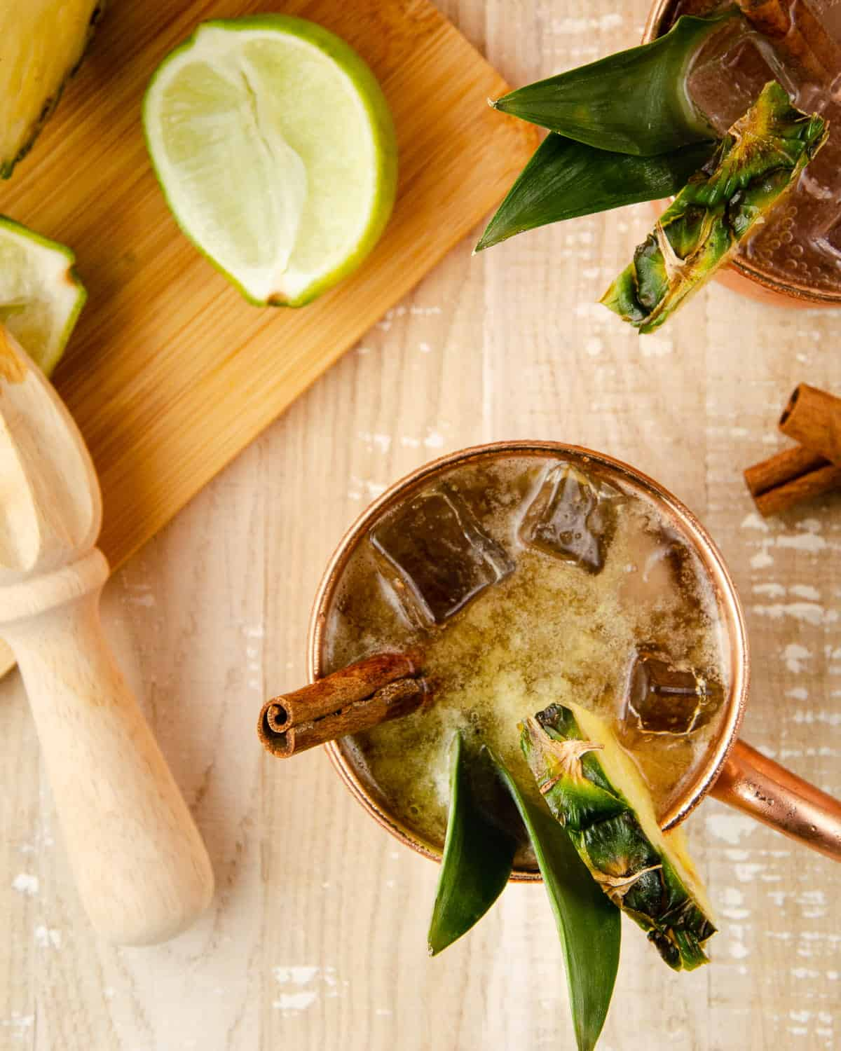overhead view of a pineapple spiced rum moscow mule: a copper mug garnished with a pineapple wedge, two pineapple leaves and a cinnamon stick. to the side is a lime wedge and a lime squeezer on top of a cutting board.