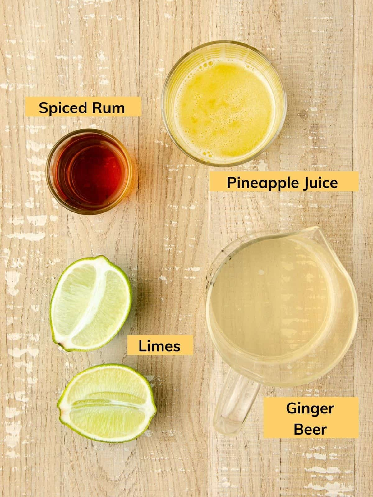 ingredients for a rum moscow mule: a bowl of pineapple juice, a shot glass with spiced rum, a lime cut in half, and a measuring cup filled with ginger beer