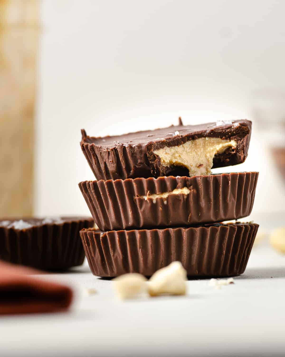 A close up of three cashew butter cups stacked vertically.