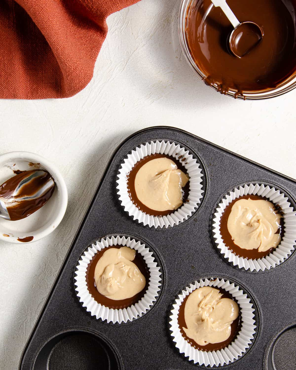 Cashew butter on top of melted chocolate for making cashew butter cups.