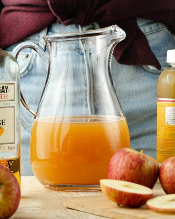 A pitcher of apple cider with a bottle of rum and a bottle of ginger kombucha to the side.