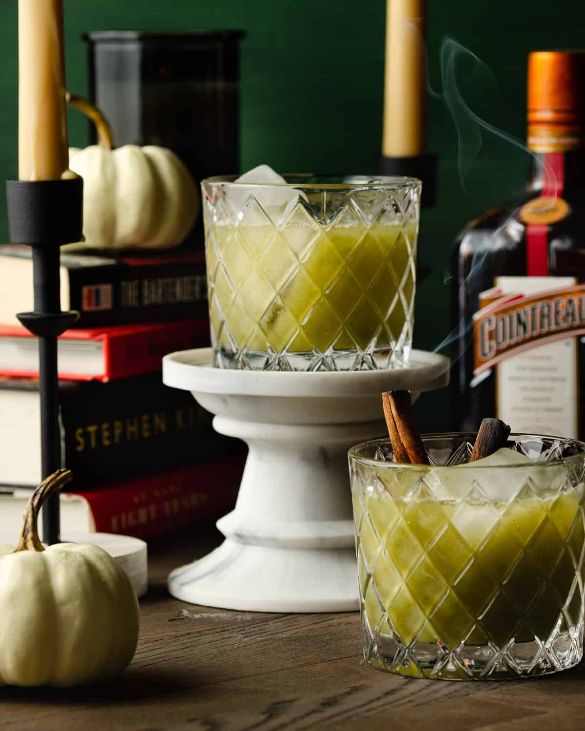 Two green Halloween cocktails with smoke coming out.