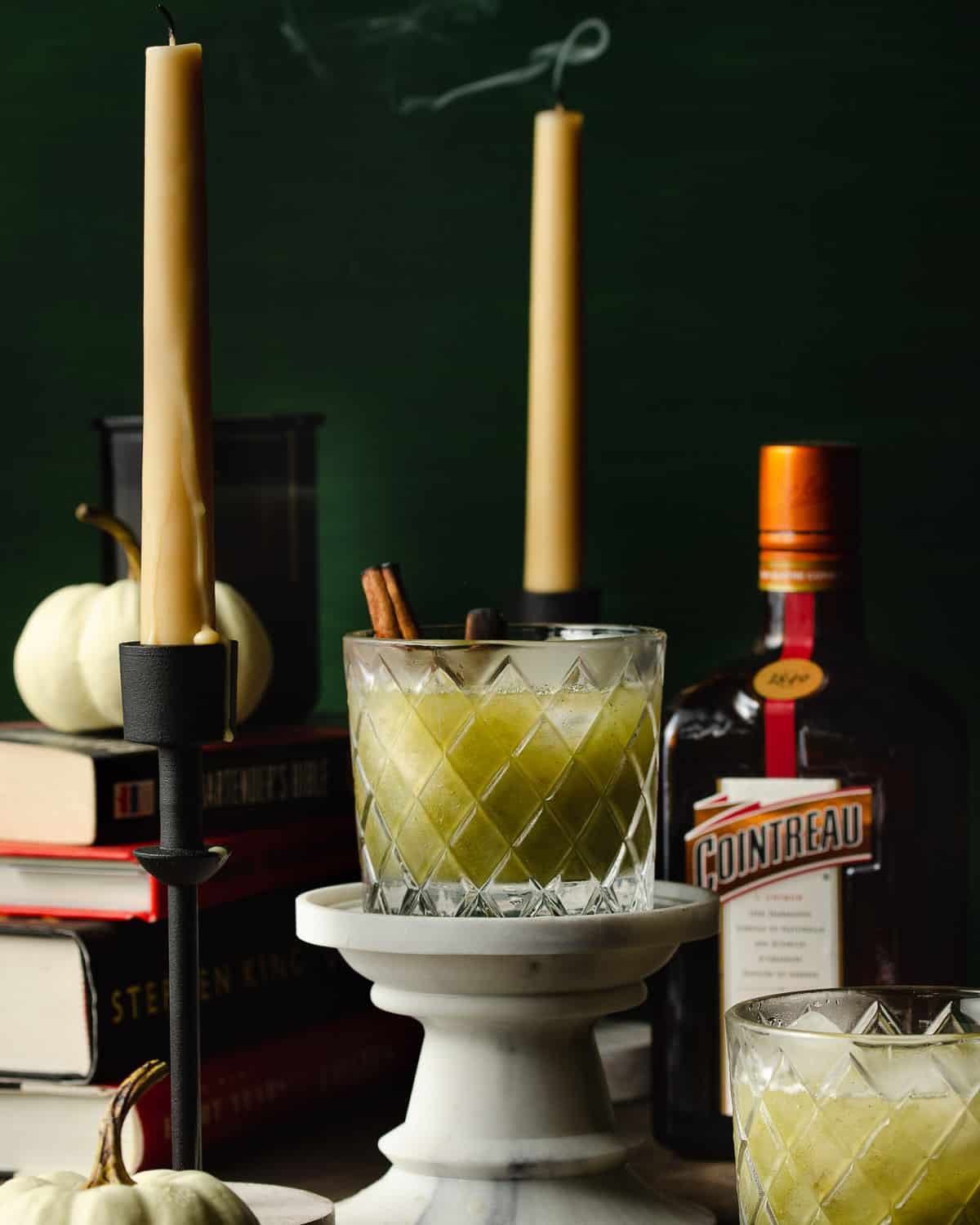 One Halloween green cocktail with a candle smoking in the back.