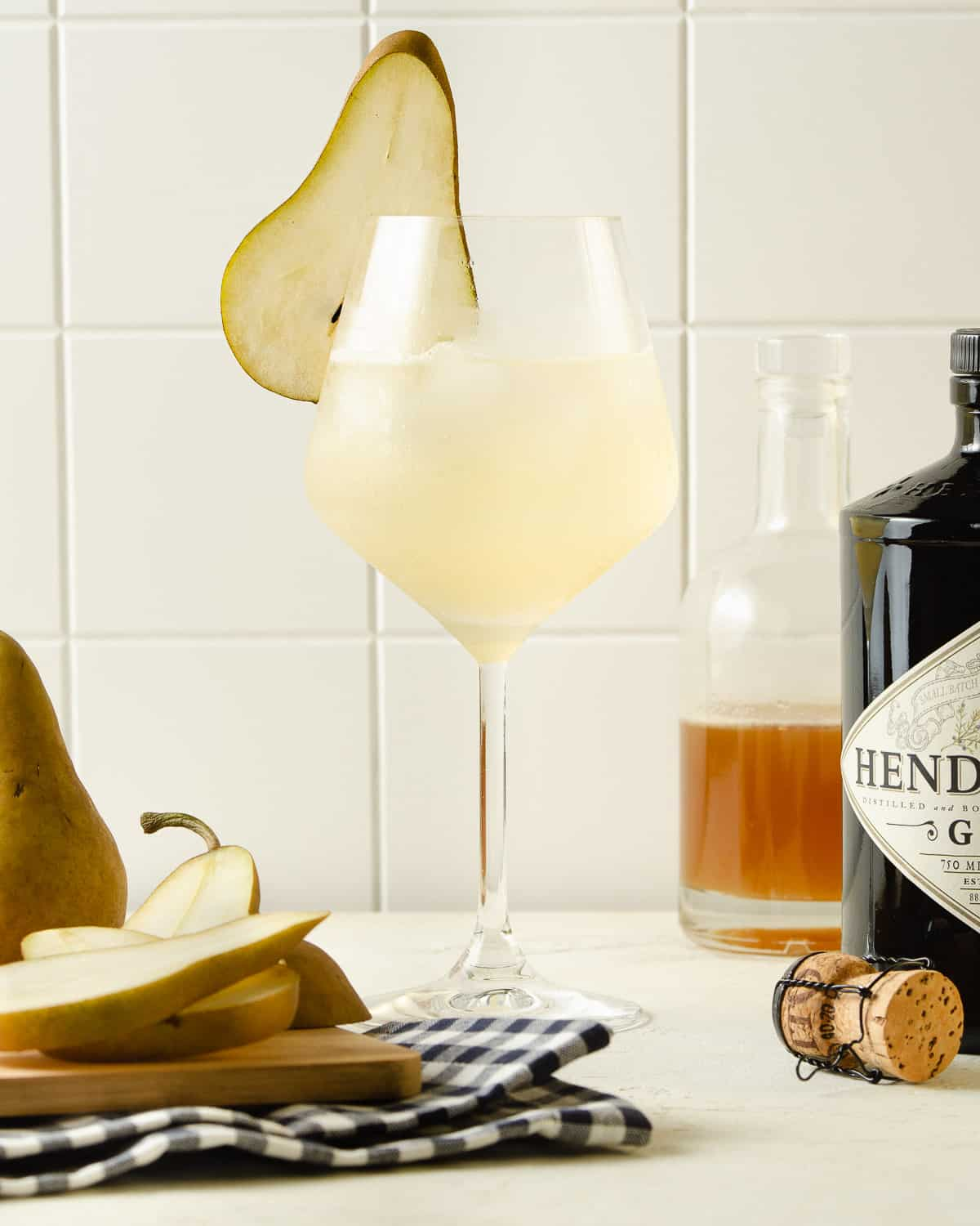 Straight on view of a pear garnish on a wine glass.