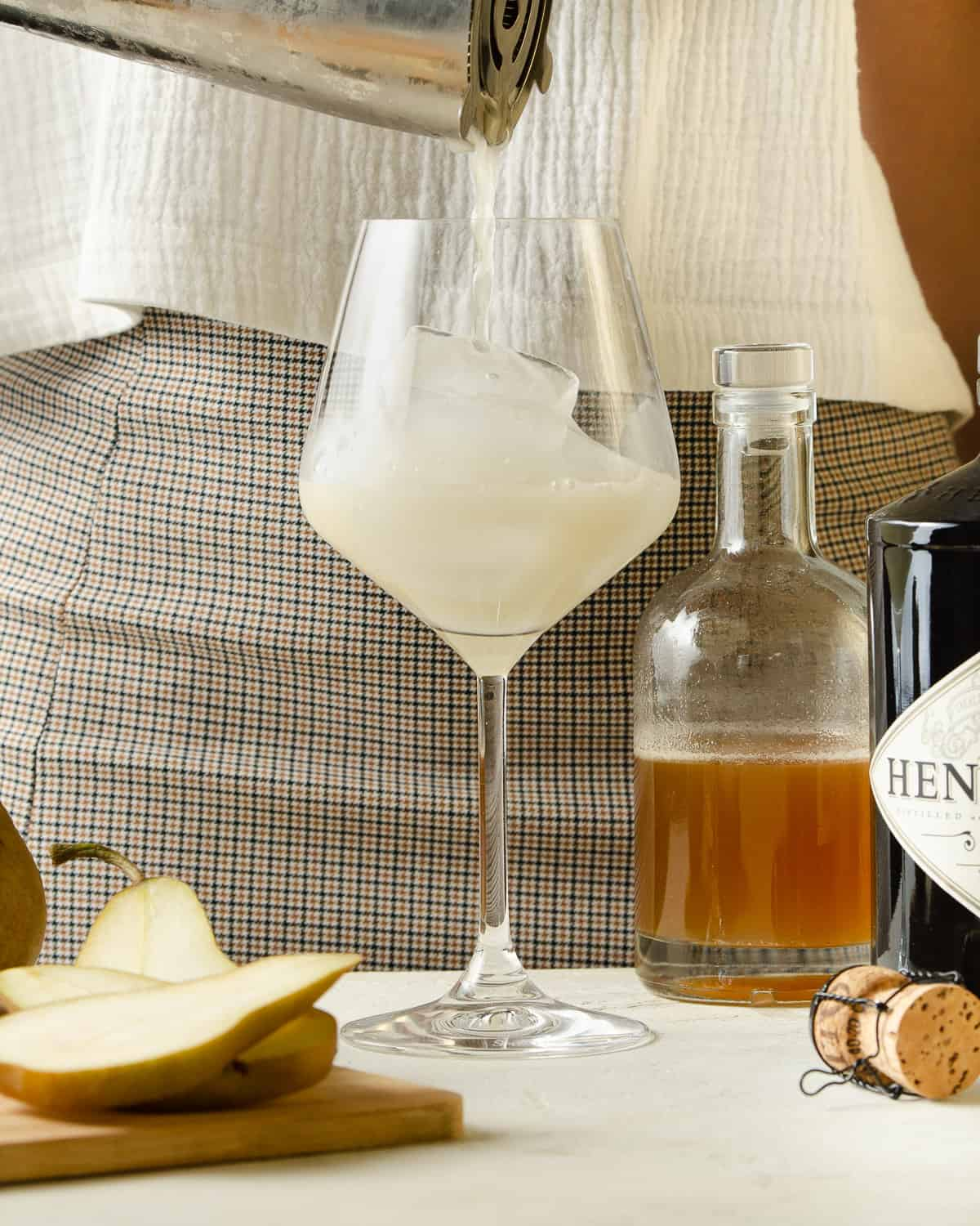Pouring a ginger gin cocktail from the shaker into a wine glass.