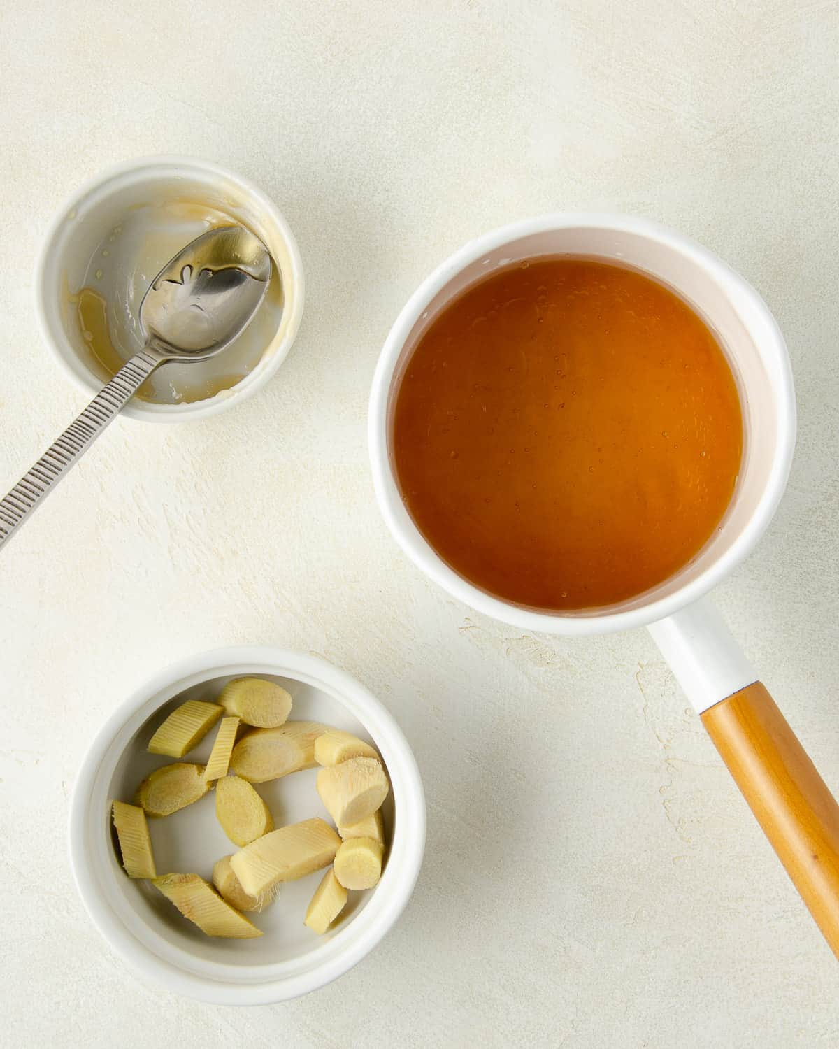 Honey and water in a small pot with sliced ginger to the side.