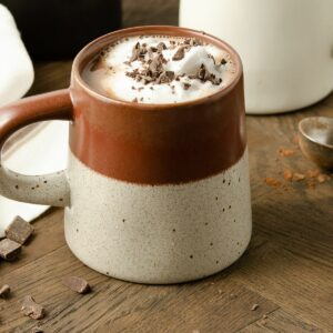A close up view of a burgundy mug filled with hot cocoa.
