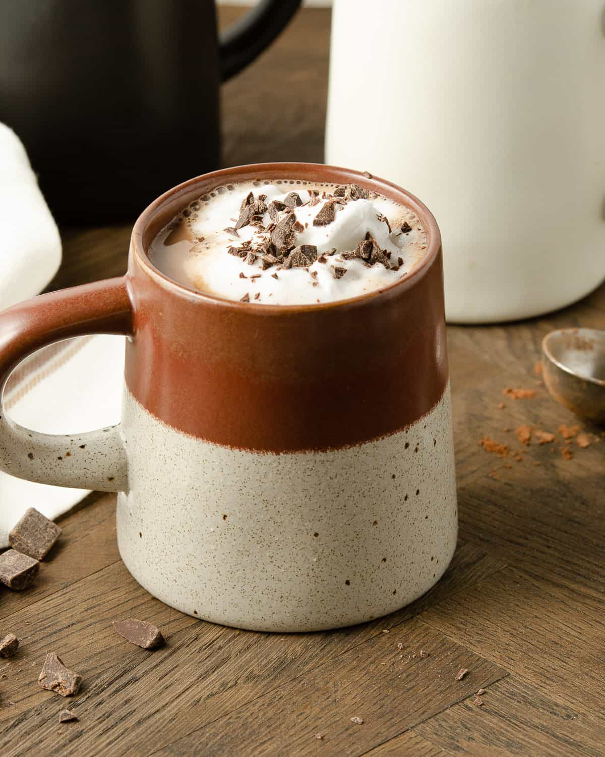 A straight on view of a burgundy mug filled with hot cocoa.