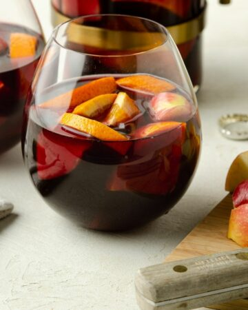 Close up of a round glass of red wine sangria.