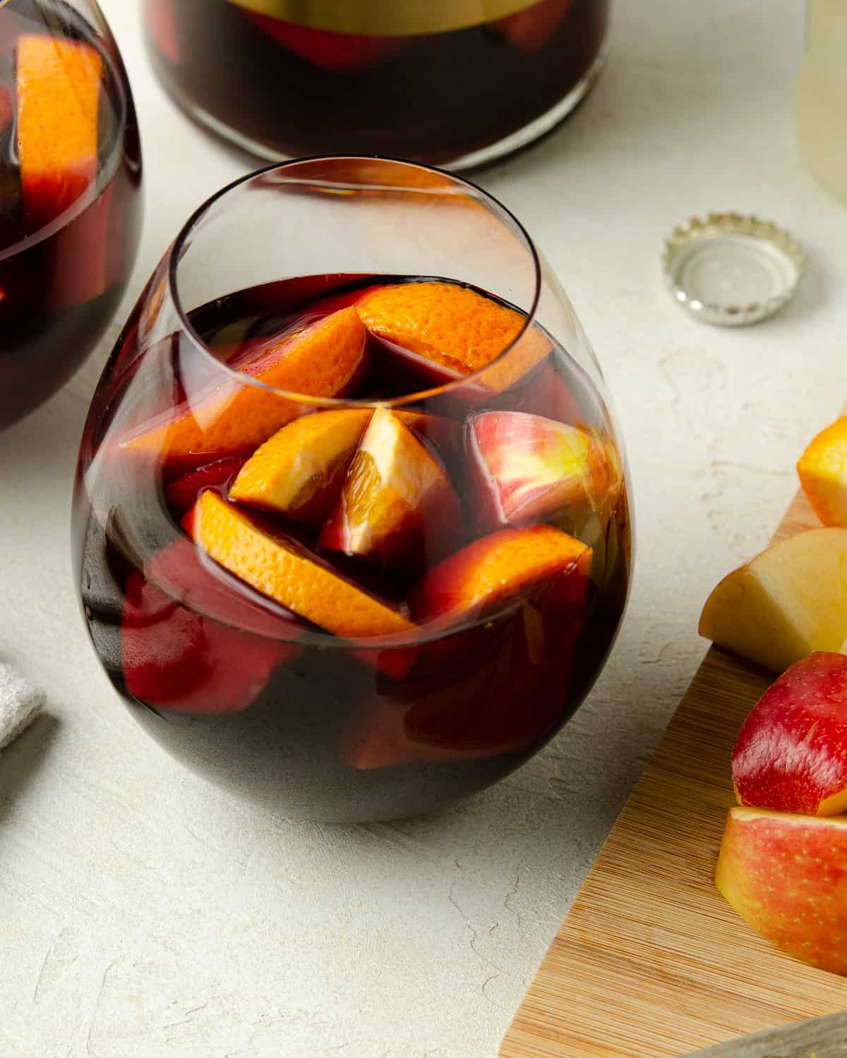 A glass of red wine sangria with apples and oranges.