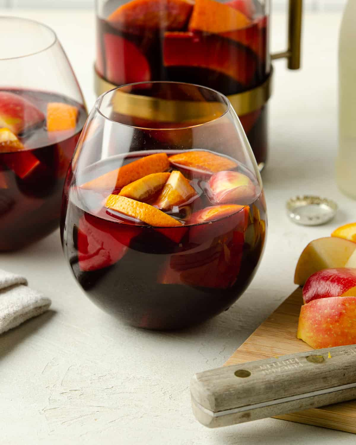 A close up of a glass of red wine sangria next to a cutting board.