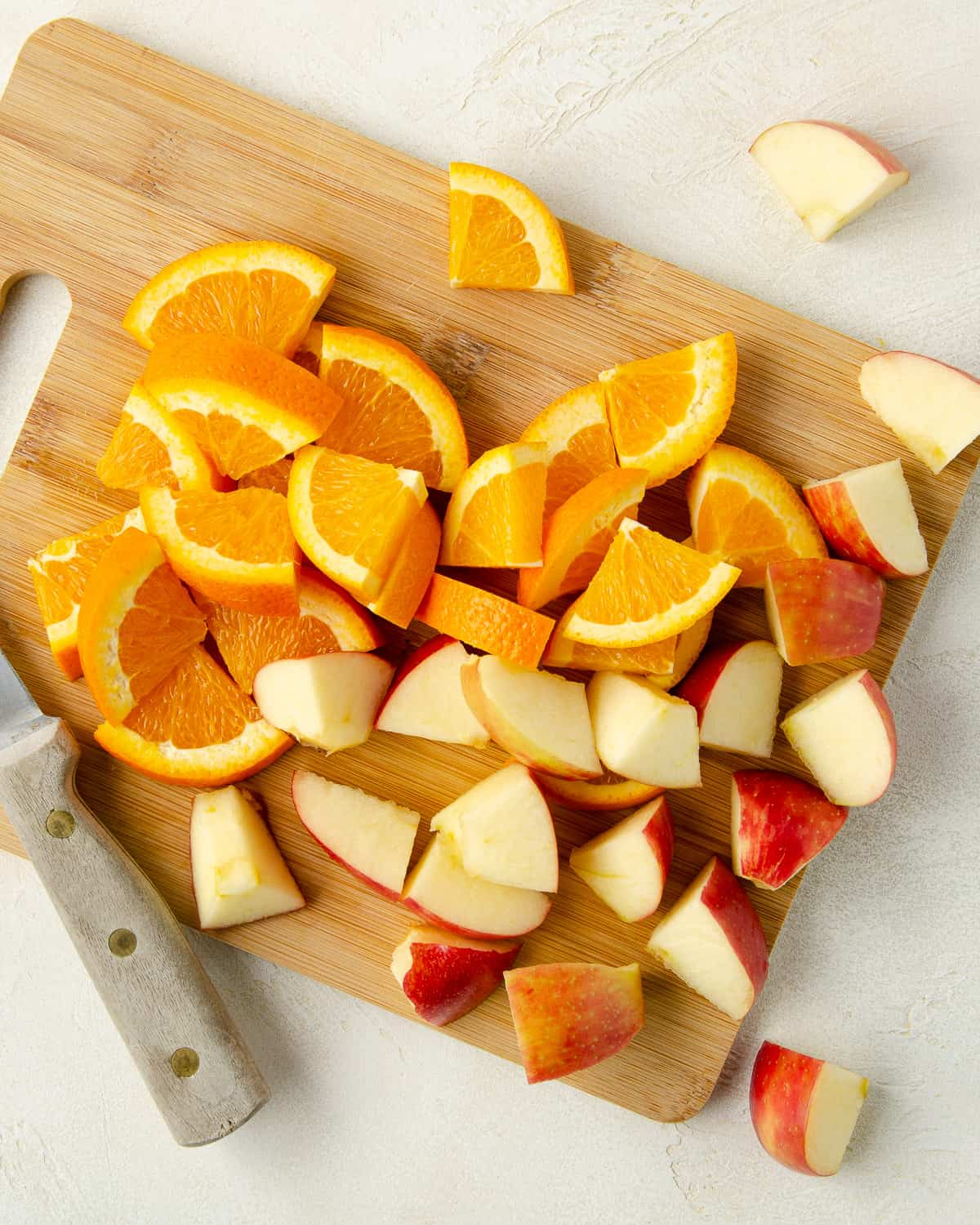 A cutting board of sliced apples and oranges.