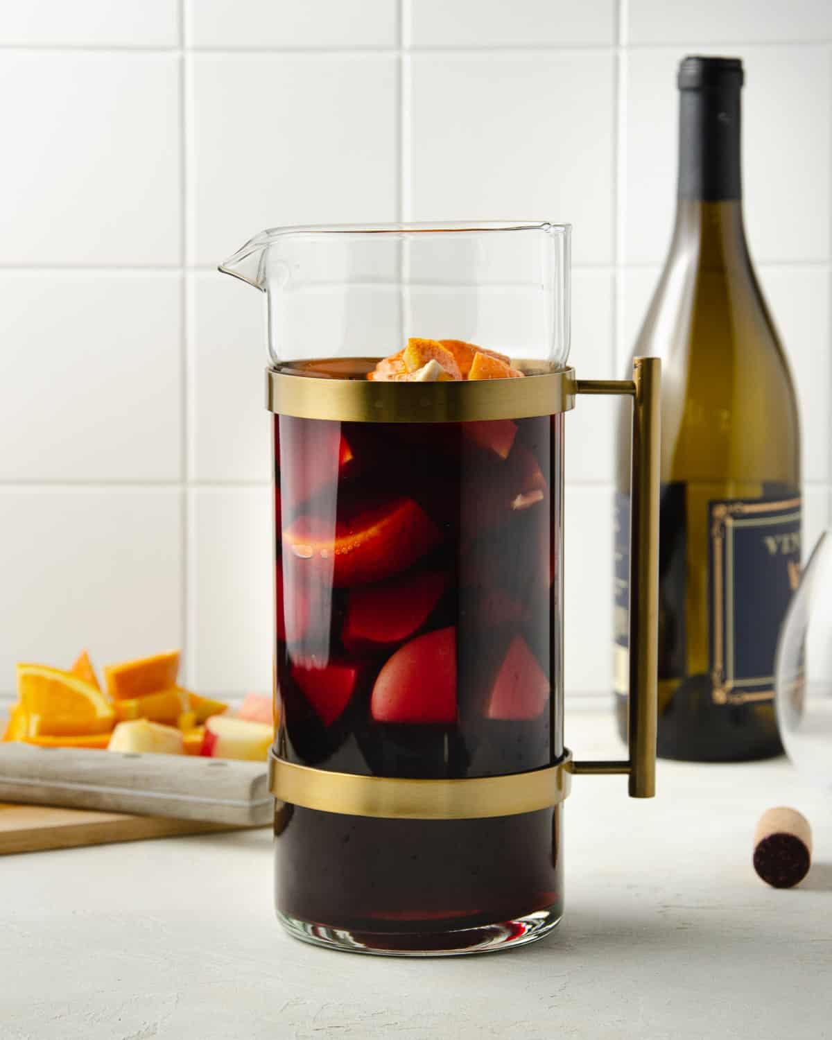 A pitcher of sangria with a bottle of wine in the back.