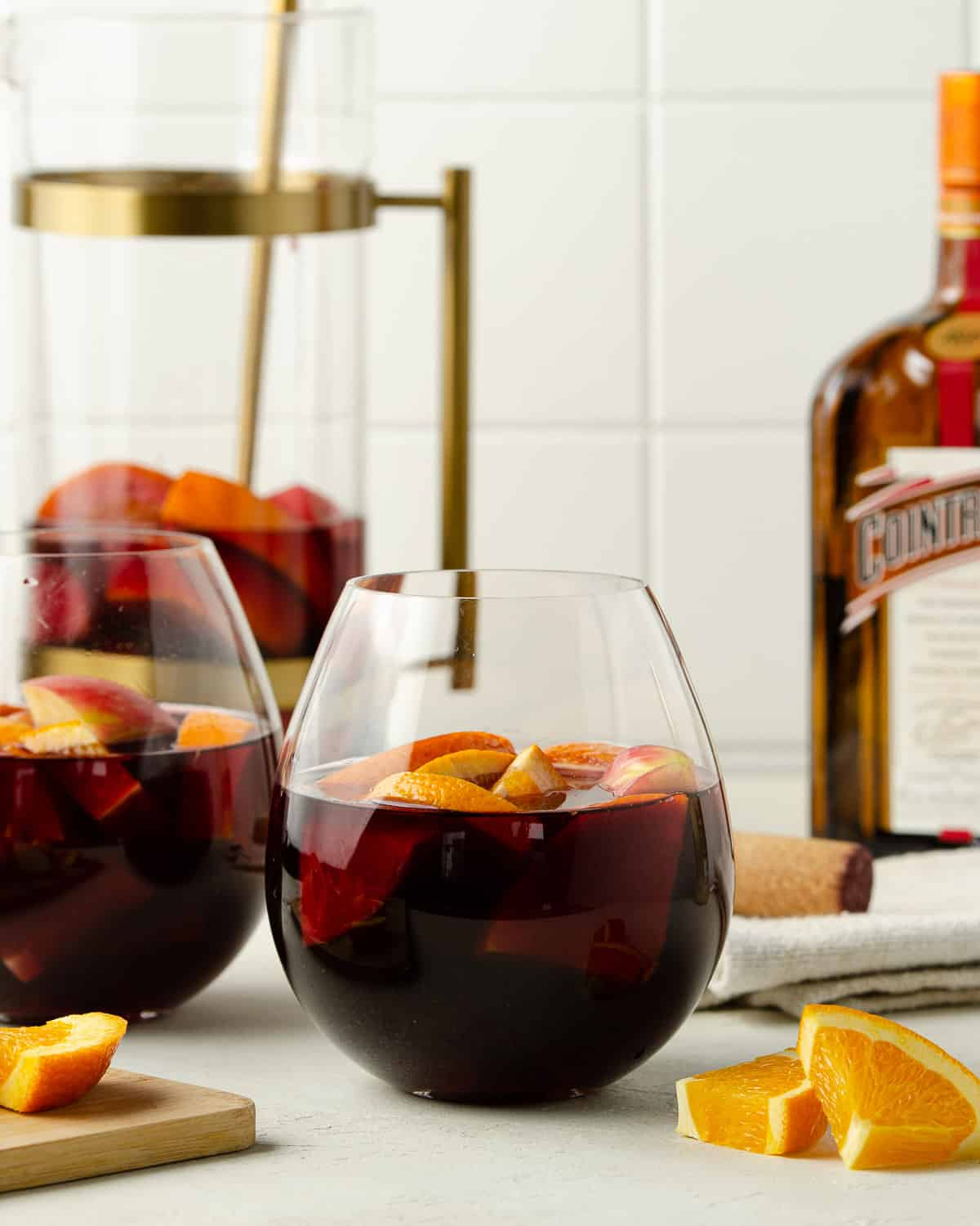 Two glasses of red wine sangria with a bottle in the back.