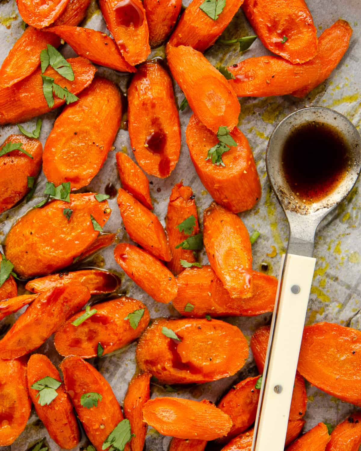 Roasted carrots on a baking tray with a spoon.