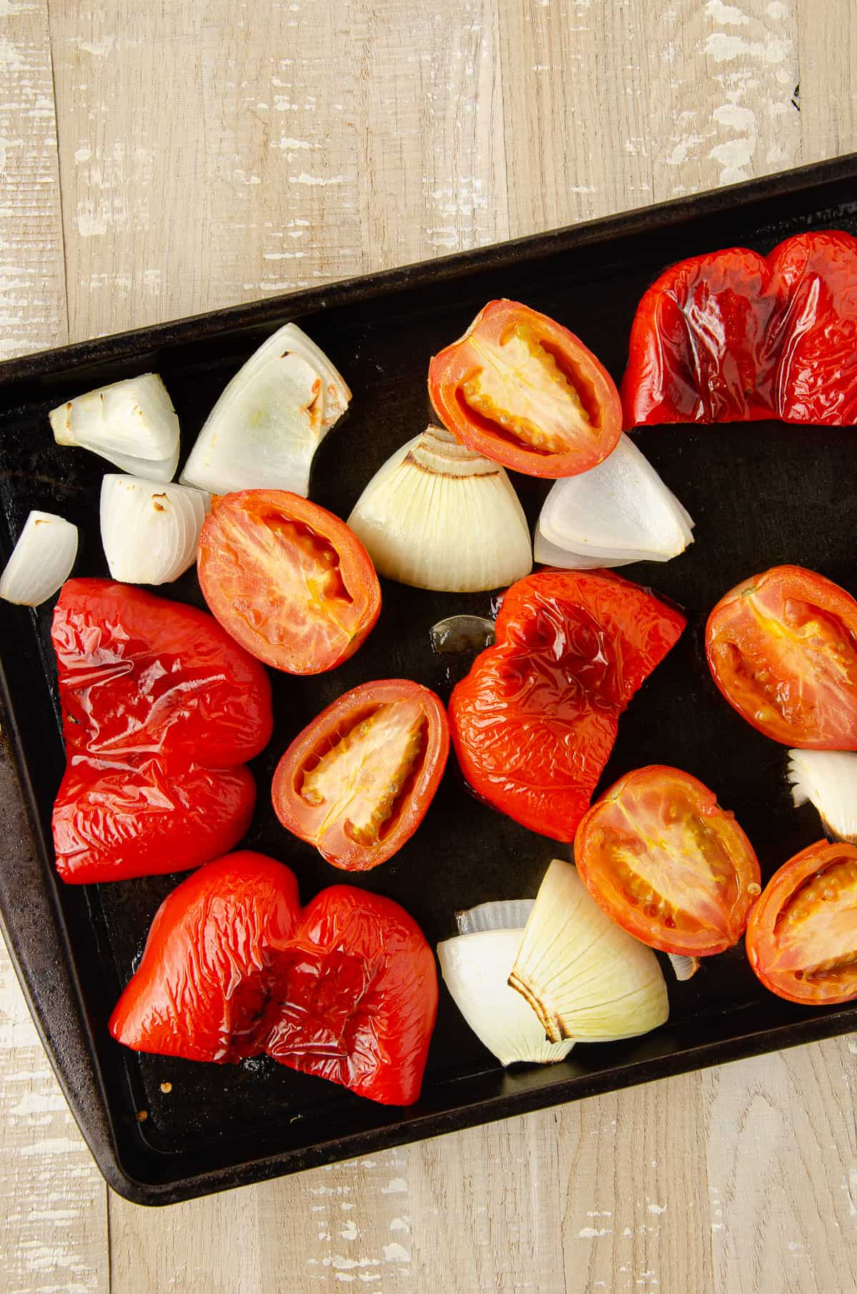 Roasted red peppers, roma tomatoes, and onion on a baking sheet.